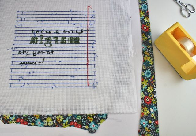 use tape to hold a cross stitch to frame mat for hanging