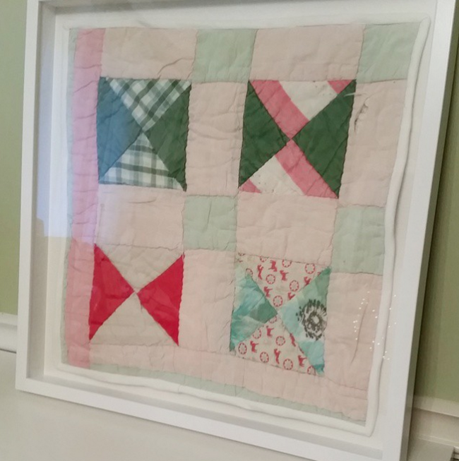 damaged quilt preserved in shadowbox